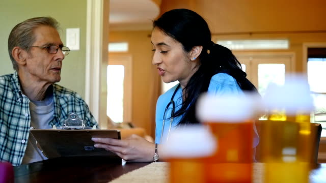 home healthcare nurse reviews plan of care with senior patient - visita a domicilio video stock e b–roll
