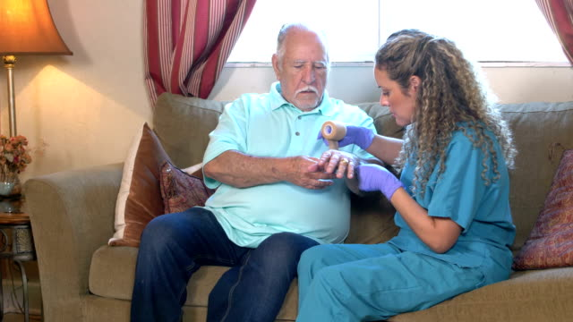 home healthcare worker bandaging senior man's wrist - bandage stock videos & royalty-free footage