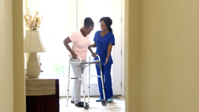 home healthcare worker helping senior woman with walker - walking frame stock videos & royalty-free footage