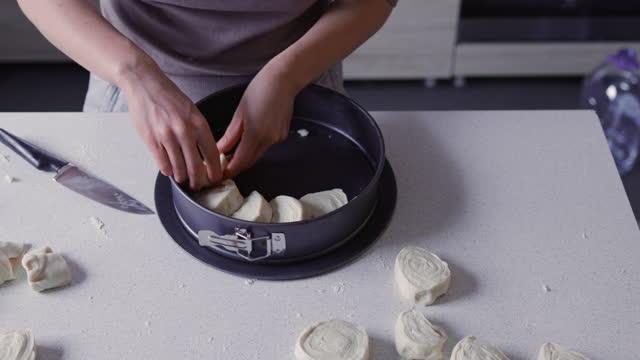 ホーム趣味:ゼロからパンを焼く匿名の女性 - ベーキングトレイにロール生地の部分を入れて - オーブンの天板点の映像素材/bロール