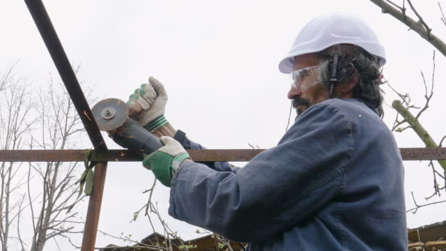 vídeos y material grabado en eventos de stock de diy. mejora del hogar. hombre mayor activo cortando barras de acero en el jardín con una amoladora angular causando chispas mientras corta el metal. - sparks