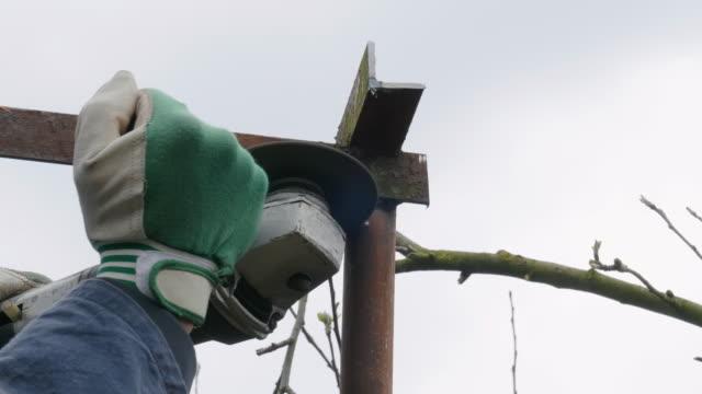 diy。改築。アクティブなシニアマンは、金属を切断しながら火花を引き起こすアングルグラインダーで庭のスチールバーを切断します。 - 日常の一コマ点の映像素材/bロール