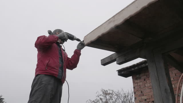 diy. home improvement. repairing the roof of the barn. active senior man working in his back yard while staying at home during covid-19 pandemic. - improvement stock videos & royalty-free footage