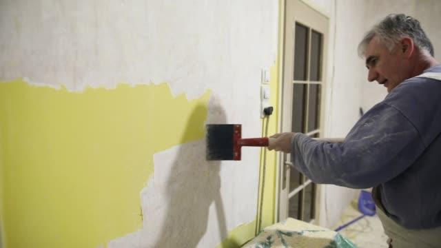vidéos et rushes de l'amélioration de l'habitat, ouvrier enlève la vieille peinture jaune du mur de béton avec le grattoir - se briser