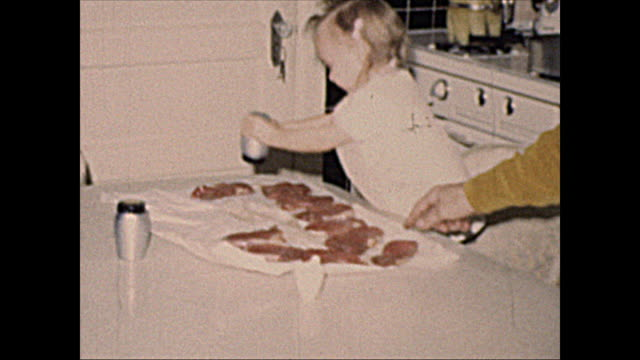 "1972 ""home movie"" 2 year old girl toddler seasoning steaks - candid stock videos & royalty-free footage"
