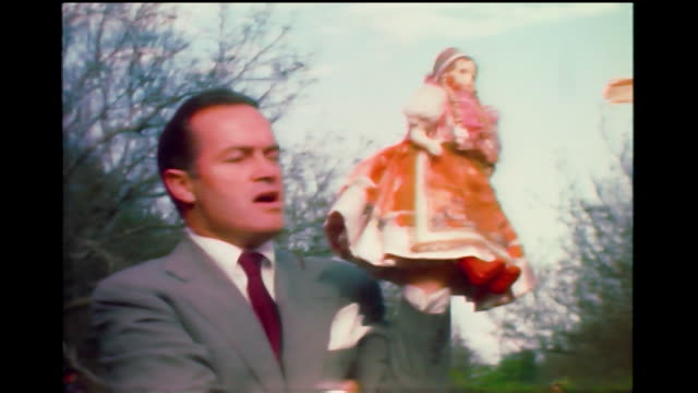 home movie bob hope holding and gesturing with a child's doll at a party in the 1940s. - fame stock videos & royalty-free footage