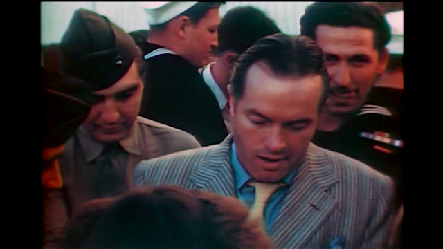home movie bob hope surrounded by fans and signing autographs for them, including military personal in hollywood 1940s. - ボブ ホープ点の映像素材/bロール