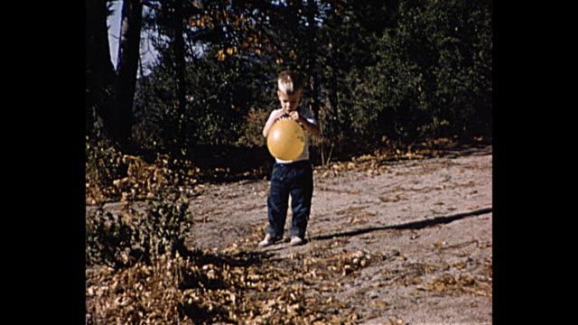 vidéos et rushes de 1958 home movie boy running around in woods holding a balloon - famille avec un enfant
