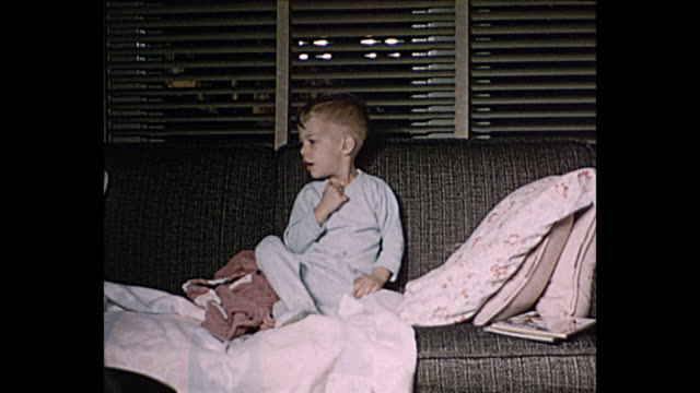 vídeos de stock, filmes e b-roll de 1958 home movie boy sleeping on sofa wakes up to help grandmother open present - home movie