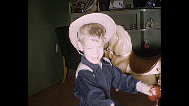 stockvideo's en b-roll-footage met 1958 home movie boy wearing a cowboy hat rides a tricycle while older sister tries to scare him - brother