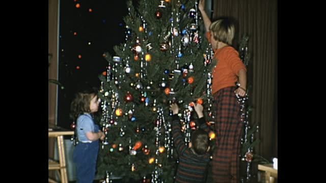 stockvideo's en b-roll-footage met 1962 home movie - children decorating christmas tree - kerstboom versieren
