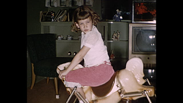 1958 home movie children playing in living room with rocking horse, tricycle, boy wears a cowboy hat - tricycle stock videos and b-roll footage