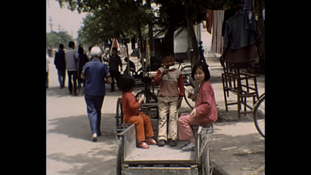 1969 home movie china children eating ice cream / women weaving / grandfather with children - chinese culture stock videos & royalty-free footage