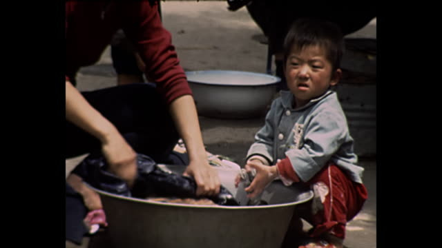 stockvideo's en b-roll-footage met 1969 home movie china /  people doing laundry - communisme