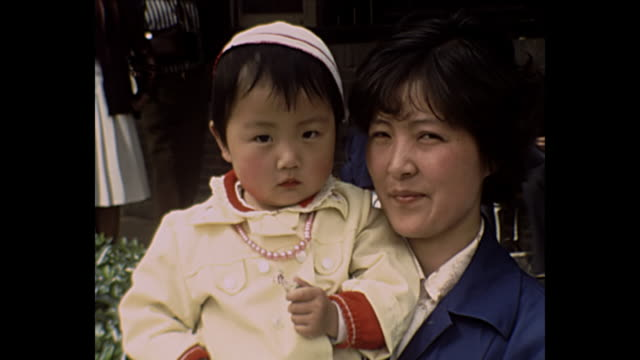 1969 home movie china  - young woman with baby - familie mit einem kind stock-videos und b-roll-filmmaterial