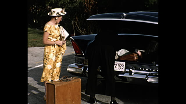 1958 home movie couple pose for camera with their new car - motel stock videos & royalty-free footage