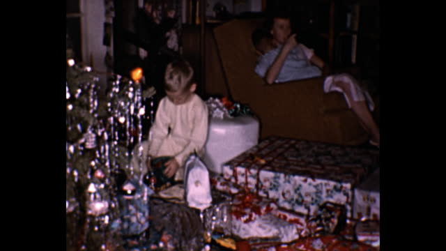 vídeos de stock, filmes e b-roll de 1959 home movie - family opens christmas presents by christmas tree - home movie