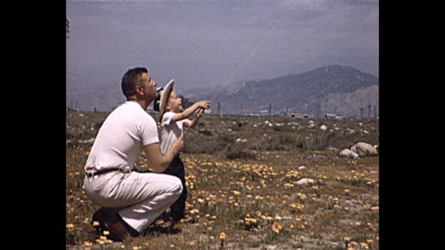 vídeos de stock, filmes e b-roll de 1958 home movie father teaches son how to fly a kite - fora de moda estilo