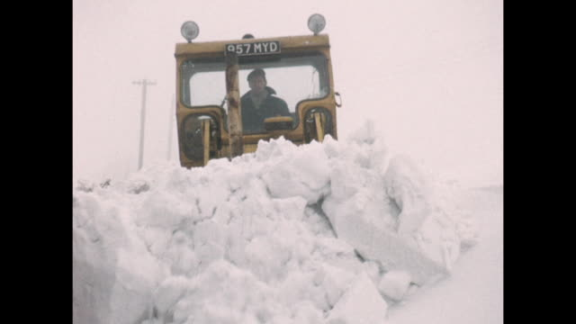 home movie footage circa 1963. known to be one of the united kingdom's coldest winters on record. an earth mover is used to dig out rural roads from... - 1963 stock videos & royalty-free footage