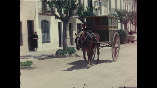 Home movie footage featuring a horse and carriage driving through a small street in the Spanish seaside town of Sitges circa August 1958