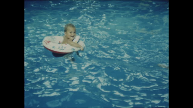 stockvideo's en b-roll-footage met home movie footage of a young boy floating with a rubber ring in a swimming pool circa 1965 - rubber ring