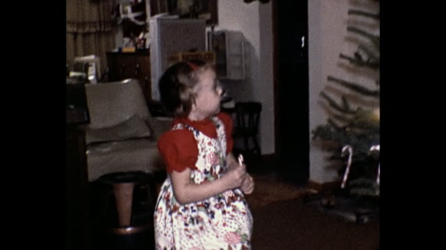 stockvideo's en b-roll-footage met 1973 home movie girl decorates christmas tree - kerstboom versieren