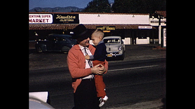 1958 home movie grandfather carrying child with classic cars in background - 1958 stock videos & royalty-free footage