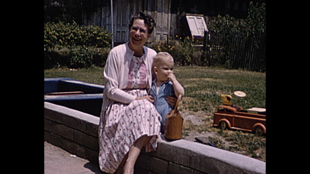 vidéos et rushes de 1958 home movie grandmother with grandchild, children with toys. boy with tricycle - grand mère