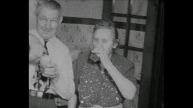 1948 home movie - grandparents toasting and drinking beer during family reunion - 移動圖像 個影片檔及 b 捲影像