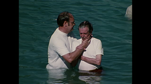 1969 home movie israel - adults get baptized in river - cristianesimo video stock e b–roll