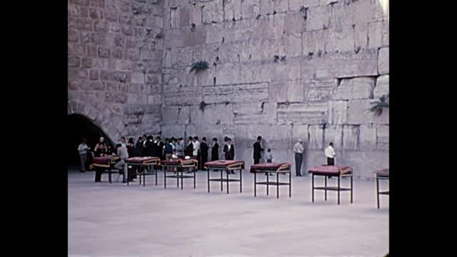 1969 home movie israel - men praying at wailing wall wide and medium shots - stone wall stock videos & royalty-free footage