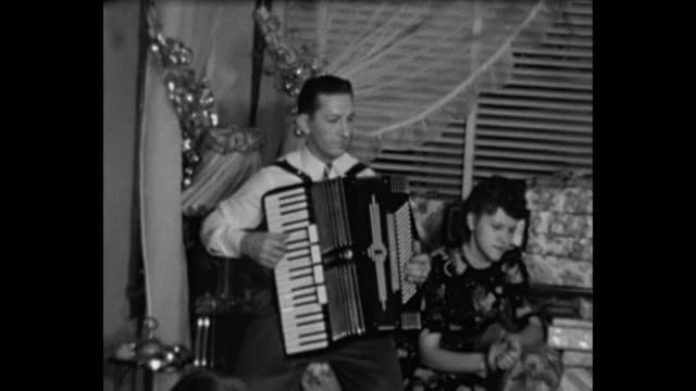 1948 home movie - man plays accordion while grandparents dance during christmas eve family reunion - home movie stock videos & royalty-free footage
