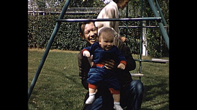 vídeos y material grabado en eventos de stock de 1958 home movie man plays with baby on swings in their front yard - father day