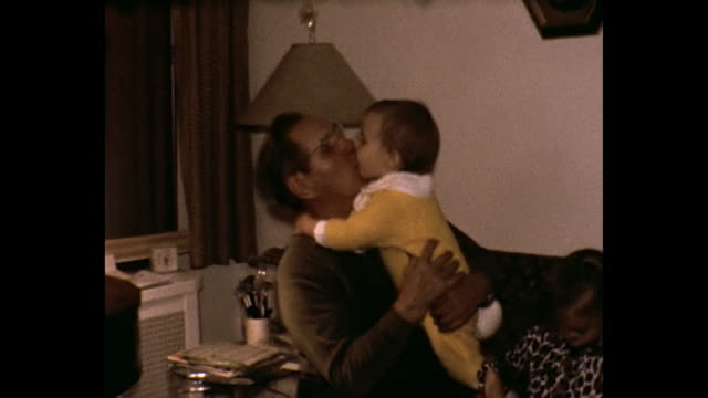 1975 home movie - man receives kisses and birthday presents by grandaughters - anno 1975 video stock e b–roll