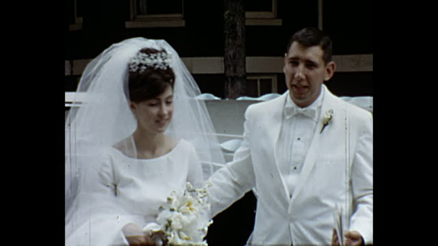 1966 home movie - newlywed couple coming out of church while guest throw rice - married stock videos & royalty-free footage
