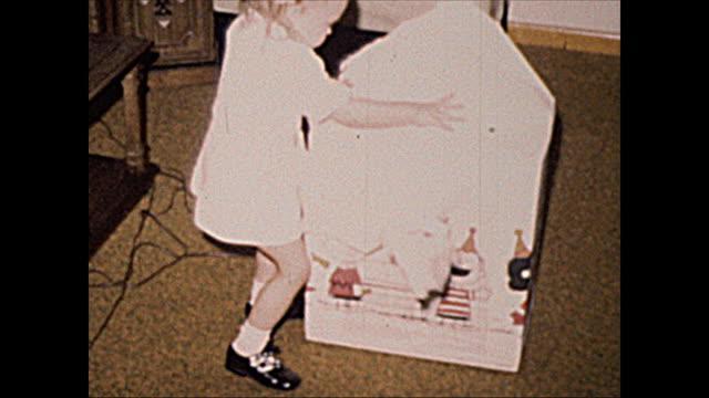 stockvideo's en b-roll-footage met 1972 home movie of 2 year old girl opening presents and playing with toys - verjaardagskado