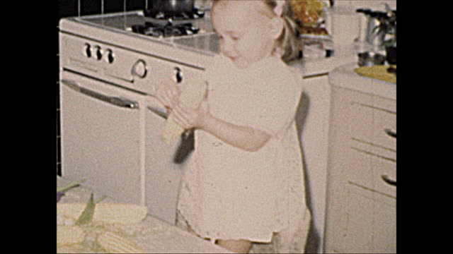 1972 home movie of 2 year old girl peeling corn - candid stock videos & royalty-free footage