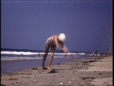 Home movie of a 15 year old Marilyn Monroe at the beach wearing a white bikini She does cartwheels and poses for a photograph with the younger...