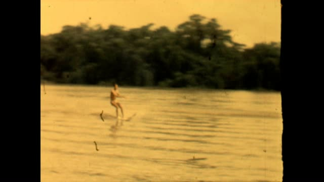 vidéos et rushes de home movie of a man enjoying water skiing on a lake in south africa in the 1960's - nostalgie