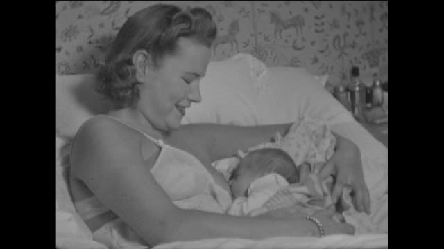 home movie of a young woman breastfeeding her newborn baby, circa 1950. - social history stock videos & royalty-free footage