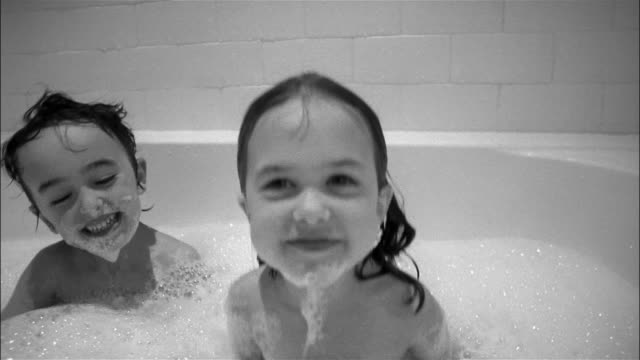 vídeos de stock, filmes e b-roll de home movie of girl and boy taking bubble bath / girl rubbing suds on her chin - 4 5 anos