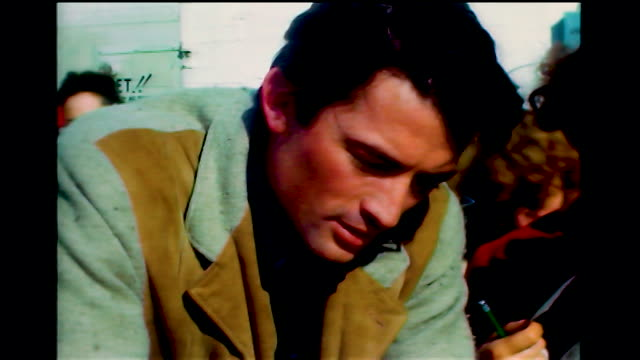 vidéos et rushes de home movie of gregory peck on the streets of hollywood surrounded by some fans who want his autograph he signs a few - autographe