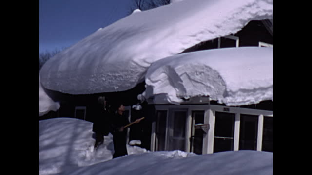 1965 home movie - people removing heavy snow from rooftop - spade stock videos & royalty-free footage