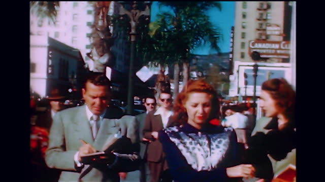 vídeos de stock, filmes e b-roll de home movie ws of phil harris walking down the street with an actress signing autographs in the 1940s - atriz