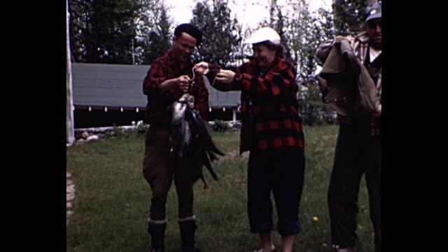 vídeos de stock e filmes b-roll de 1955 home movie - posing for camera with fish - amanhar o peixe