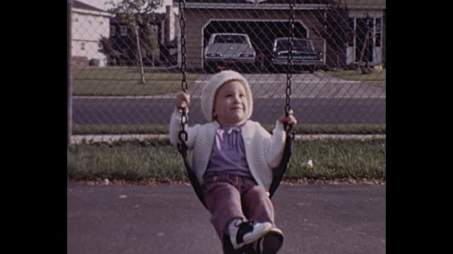 1972 home movie - toddler girl on playground swing with mom - home movie video stock e b–roll