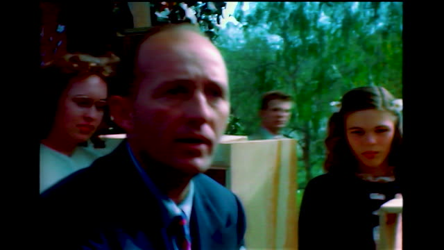 home movie view of bing crosby without his toupee hitting a pinata while a photographer shoots pictures in the background. more cus of bing writing... - papier stock videos & royalty-free footage