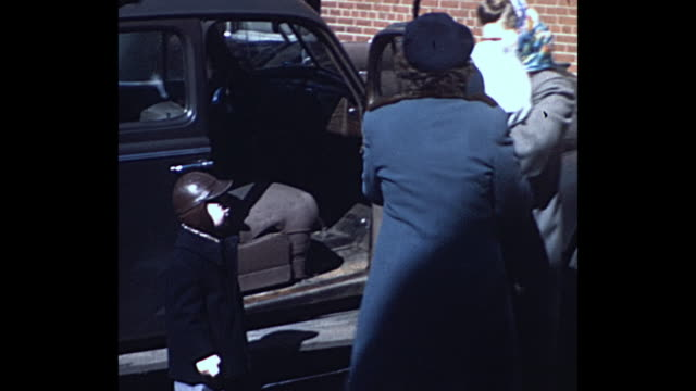 1948 home movie - women wearing winter coats get in car with baby and young boy - helgdag bildbanksvideor och videomaterial från bakom kulisserna