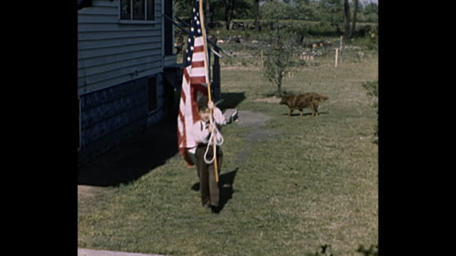 vídeos de stock e filmes b-roll de 1948 home movie - young boy carries  american flag front backyard to the house porch - patriotismo