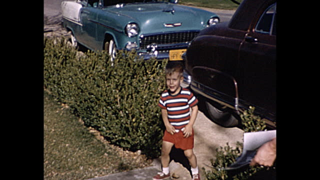 1958 Home Movie Young Boy in front yard with father smoking cigarrette